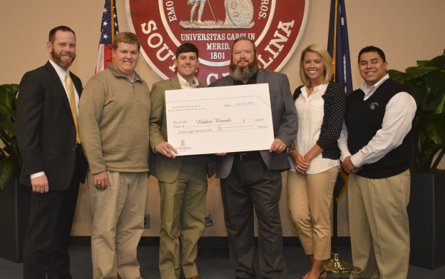 Left to right, Members of SVL Michael Bradbury (2015), Ryan Templeton (2014) and John Wall (2015) present a check to Hidden Wounds board members Freddie Brock, US Army (Ret.) and Steven Diaz, USMC (Ret.). Also pictured is Ashley Canara, a senior public relations student at USC and a volunteer with Hidden Wounds.